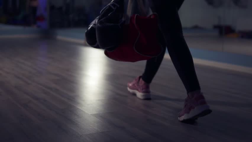 Closeup view of legs of young fit woman entering a fitness club with a bag and boxing gloves and preparing for the training in a boxing club.