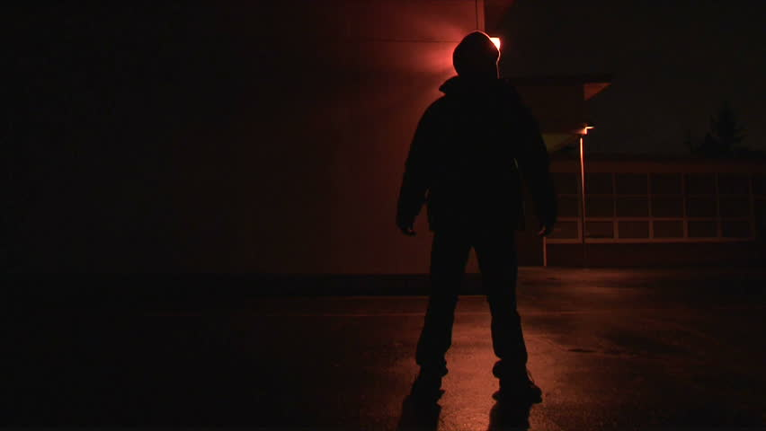 Person disappears and reappears exterior, night, then walks towards camera