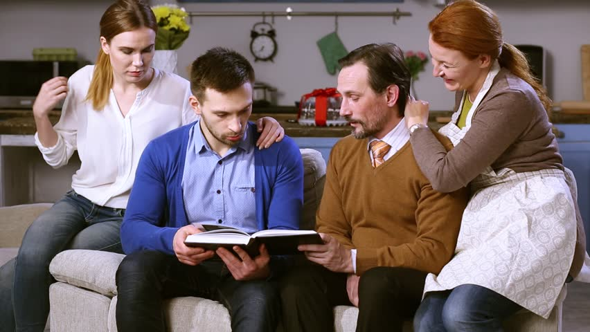 Parents showing family album to their daughters boyfriend. close up portrait of two genertions couple sitting on couch, sharing memories. | Shutterstock HD Video #28401811