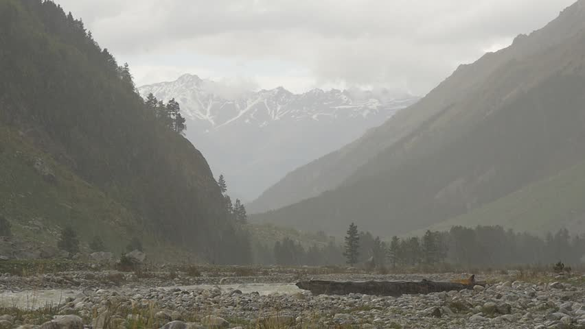 Storm in mountains. Rain with hail in slow motion