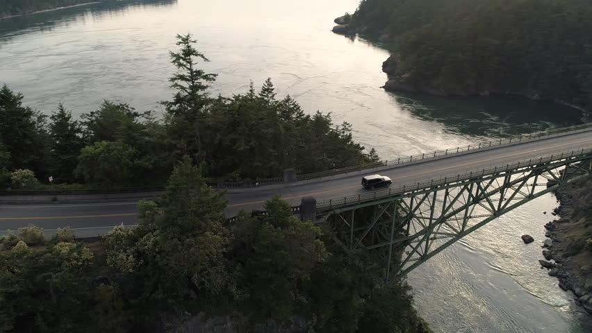 Transportation Aerial Establishing Road Trip with Black SUV Truck Driving Across High Bridge to Ocean Background | Shutterstock HD Video #28409488