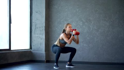 Young fitness woman doing squat with dumbbells in hands. Scene in the gym. Woman in sportswear with pink dumbbells