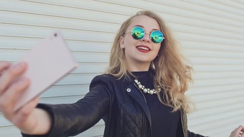 A stylish young blonde in a leather jacket and sunglasses takes a photo from a mobile phone near the horizontal roller blinds.