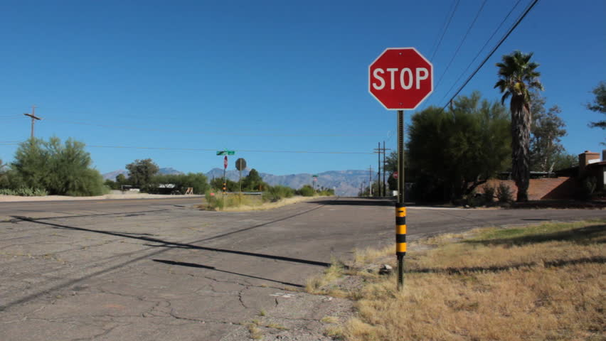 Stop Sign on Side Road as Traffic Moves By - People driving their cars by a side road with a stop sign.