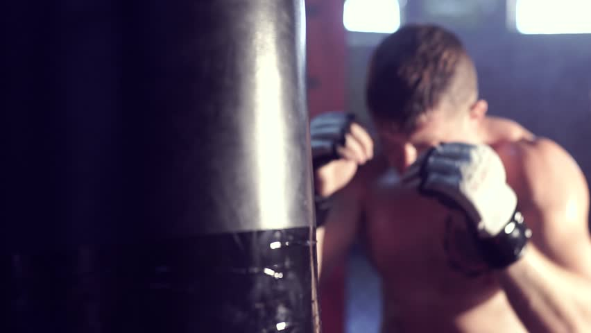 Young male boxer hitting punching bag, smoke on background. Slow motion. | Shutterstock HD Video #28473328