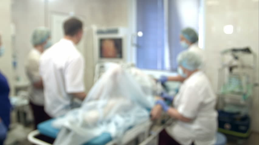 Doctors and nurses performing endoscopic procedure in hospital