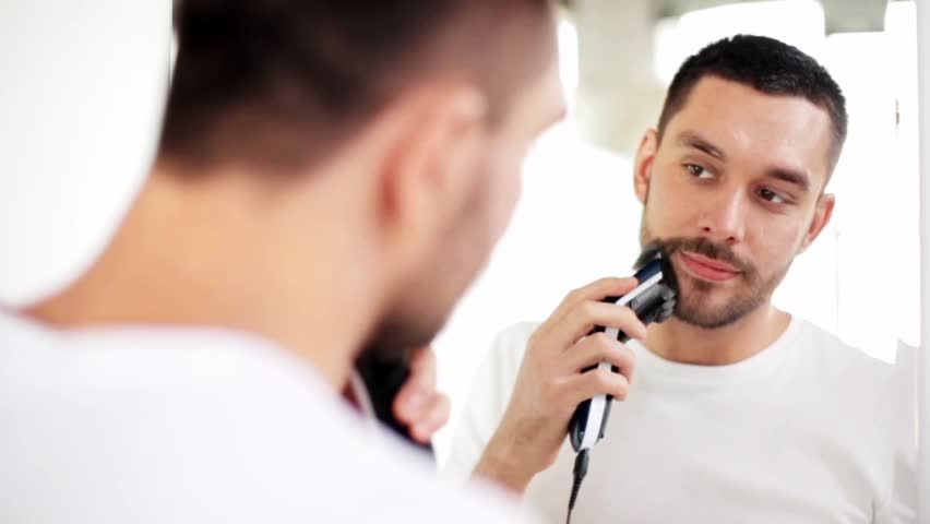 beauty, grooming and people concept - young man looking to mirror and shaving beard with trimmer or electric shaver at home bathroom