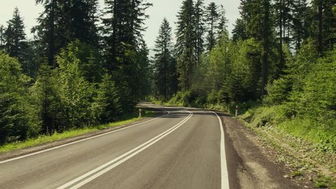 Car road bend in mountainuos forest and speed limit sign. 4K gimbal stabilized travelling shot