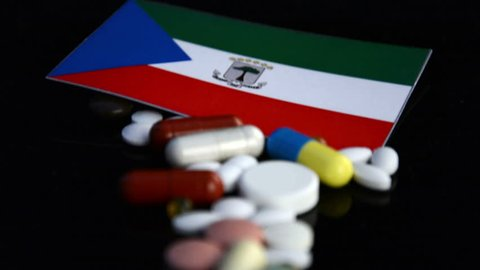 Equatorial Guinea flag with lot of medical pills isolated on black background