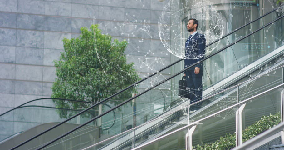 A businessman the stairs are coming down in a suit uses holography and augmented reality to see in 3D graphics financial economics. Concept: immersive technology, business, economy, futuristic | Shutterstock HD Video #28530568