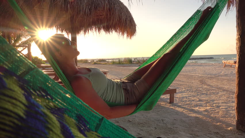 CLOSE UP: Happy young woman on vacation laying and resting in hammock at golden sunset in hot summer on Mexico beach. Serene woman relaxing in swinging hammock on sandy beach at sunrise golden light