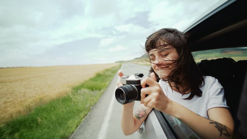 happy and excited young woman hangs out of car window, her brown hair blows in wind and she makes photos of landscapes and holiday spots on her vintage analog camera