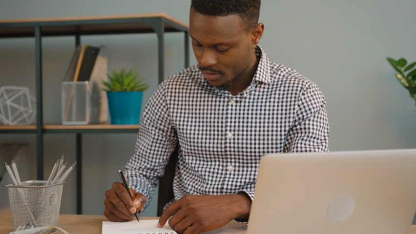 Mixed race architect in design agency working with blueprint african americam business man working at the office black man writing in the notebook from malvernweather Images