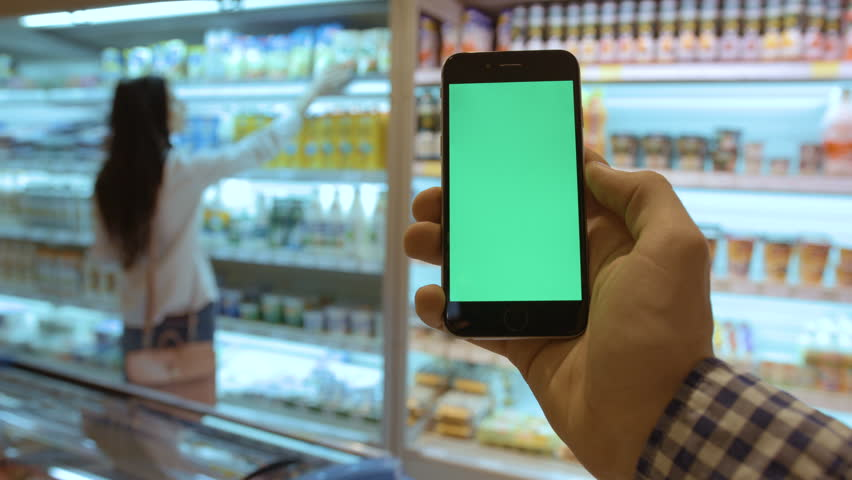 NEW YORK - January 17, 2016: Man hands using black smartphone with green screen in the super market on background with dairy product and woman who choose something. Chroma key. Green screen.