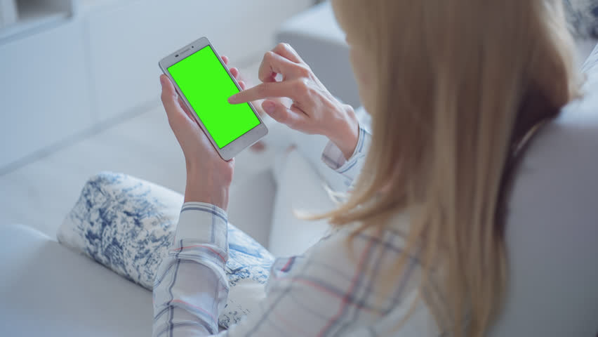 Young Woman in white jeans sitting on couch uses mobile phone with pre-keyed green screen. Few types of gestures - scrolling up and down, tapping, zoom in and out. 10bit ProRes 444 | Shutterstock HD Video #28588138