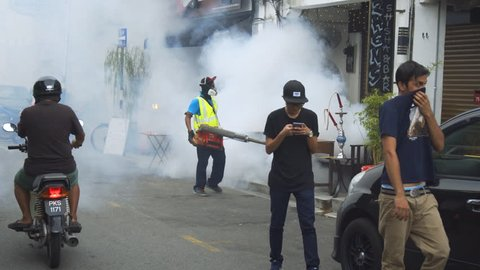 GEORGE TOWN. PENANG. MALAYSIA - CIRCA MAY 2017: Local man fumigating along a city street to stop mosquitos and the spread of Dengue Fever. UltraHD 4k video