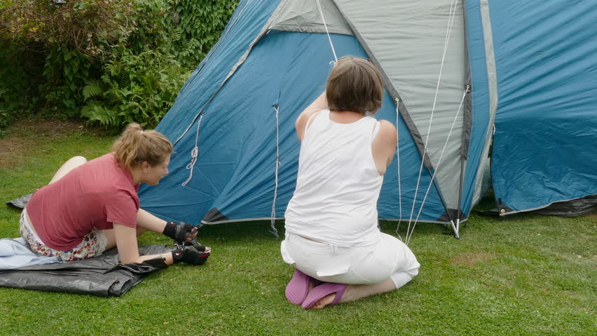 A young woman and her mother erecting a tent with their Bichon Frise dog exiting & A Young Woman Kneeling In A Newly Erected Tent Playing With Her ...