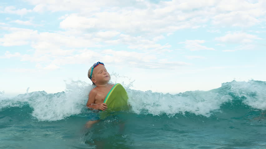little boy tries to catch a wave with swim board slow motion. boy in swimming goggles having fun in the sea with the swim board