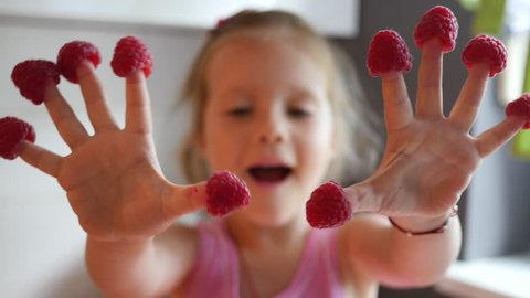 Cute little child girl portrait funny eating red raspberries putted on fingers
