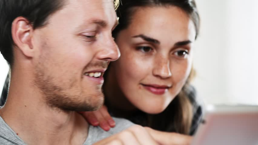 Happy couple using tablet touching touchscreen high definition video