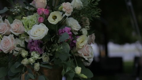 Flower Arrangement in Vase. Flower arrangement bouquet standing in vase on table. Close view of colorful flowers. Fresh pink roses, white carnation, green grass, amazing herbs. Close up