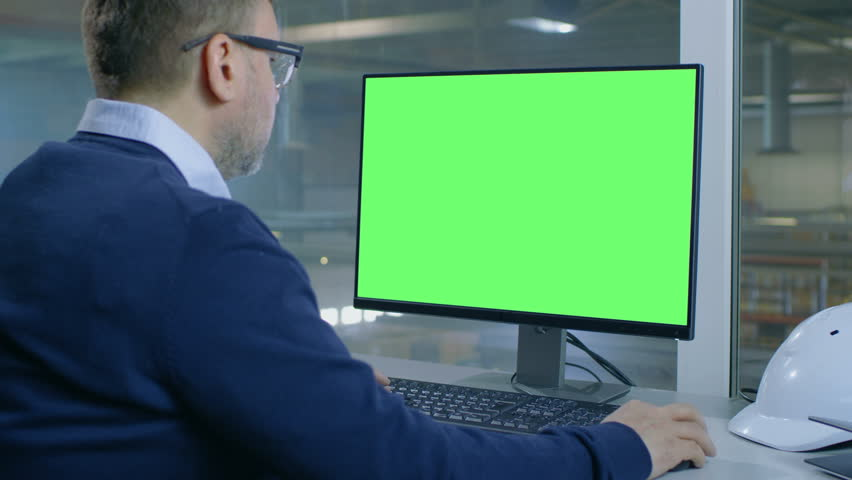 Chief Engineer Works on His Computer with Mock-up Green Screen. Inside of the Factory is Seen From Her Office Window. Shot on RED EPIC-W 8K Helium Cinema Camera. | Shutterstock HD Video #28698358