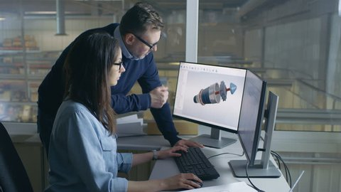 Female Industrial Engineer and Male Project Manager Work on 3D Turbine/ Engine Model in Her CAD Software. Inside of the Factory is Seen From the Office Window. Shot on RED EPIC-W 8K Helium  Camera.
