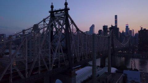dusk flying alongside Queensboro Bridge away from Manhattan
