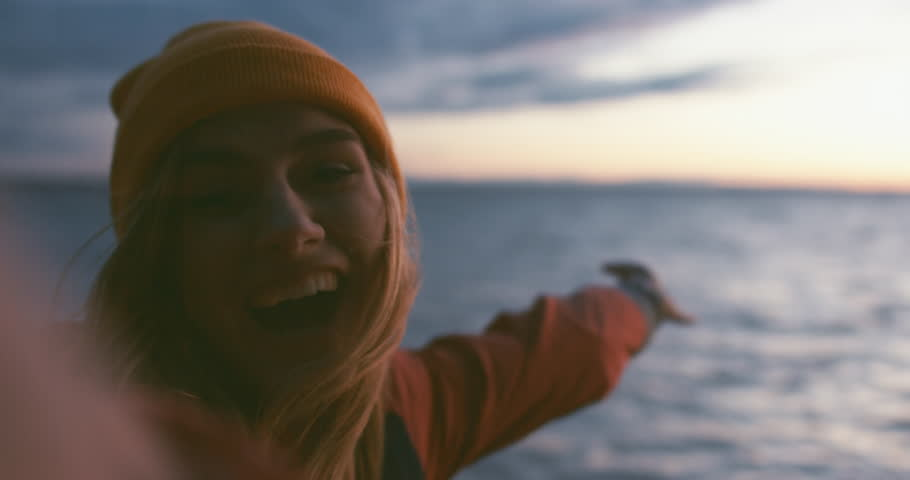 Happy Caucasian girl making selfie or a video call on a large lake, smiling and laughing into camera. Smartphone camera POV. 4K UHD