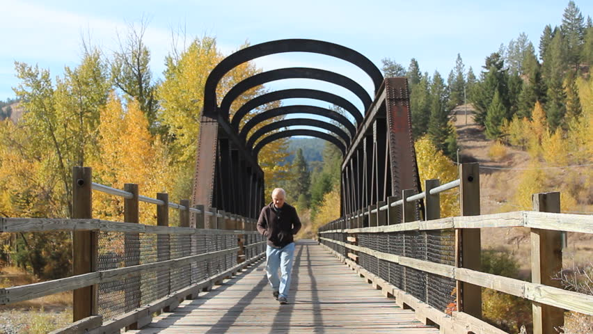A tourist walks across an old train bridge that was part of the Kettle Valley Railroad, a heritage site in British Columbia, Canada/Tourist and Rail Bridge/The Kettle Valley Railroad