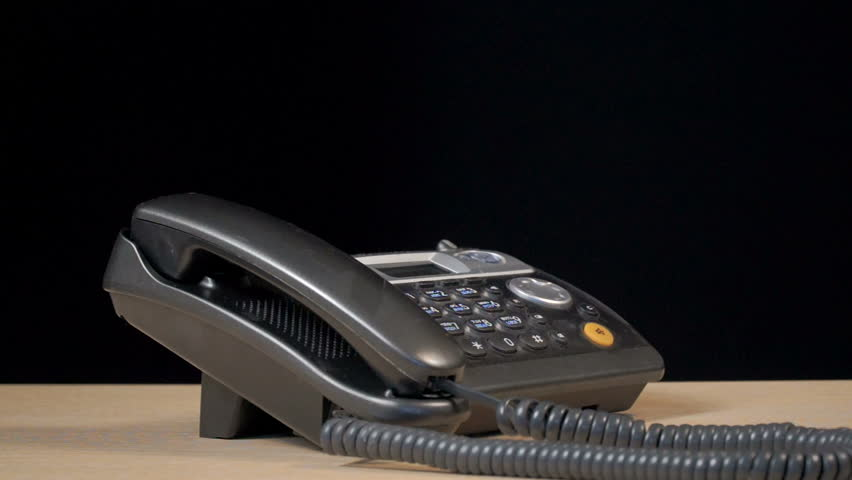 The phone in the office is on the desk. The man is using the phone. Shooting in the studio on a black background. Close-up of the hands of a man.