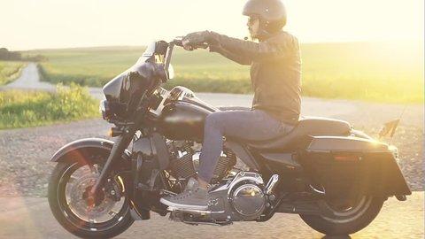 Stylish man on motorcycle in sunlight