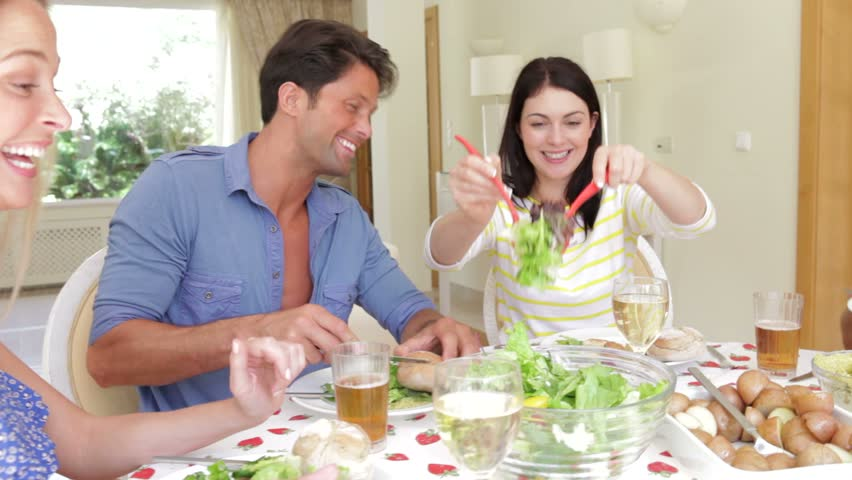 Couples seated around dining table serving one another before picking up glasses for toast.