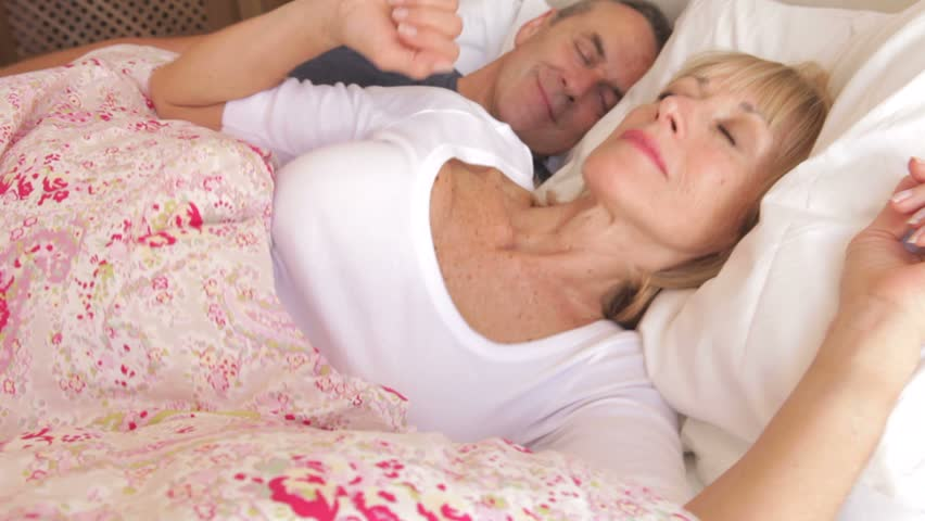 Camera tracks along bed to sleeping senior couple as woman stretches,open eyes and looks at camera.