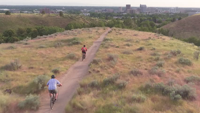 A moving aerial shot follows 2 male and 1 female mountain bikers down trail and over a small jump toward a backdrop of trees and the downtown Boise, Idaho, city skyline.