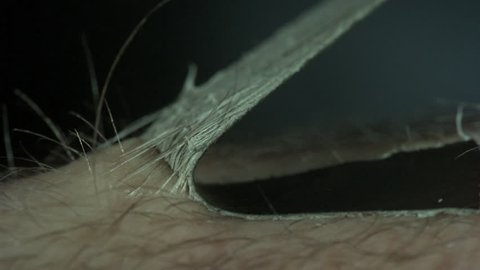 Peeling Off a Bandaid Macro - Extreme closeup with insane amount of detail as a black Band-Aid bandage is pulled off an arm in slow motion, showing the adhesive and the hairs sticking and peeling