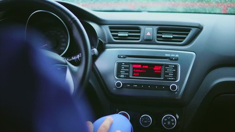 Interior of the car. Driver switching radio settings and listening the music. View on car torpedo. Selective focus.