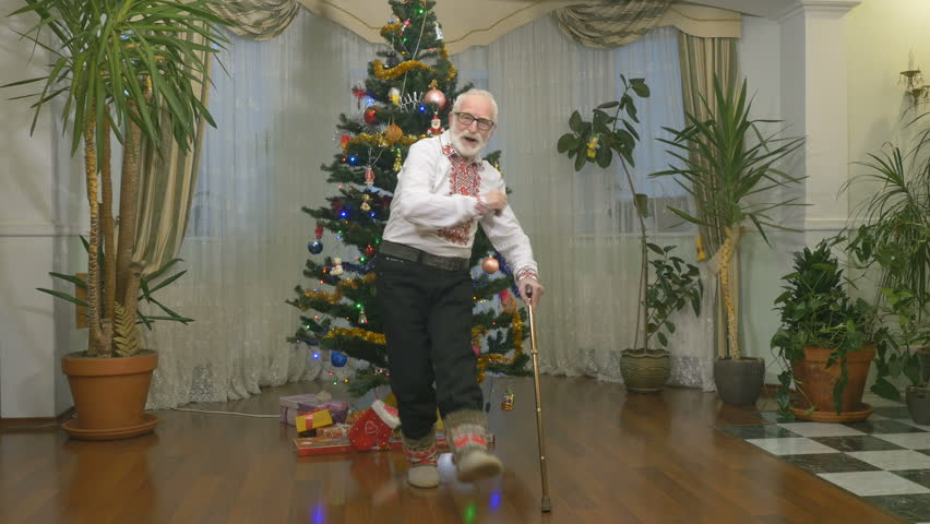 Funny Old Man Dances Near The Christmas Tree 4k Stock Video Clip
