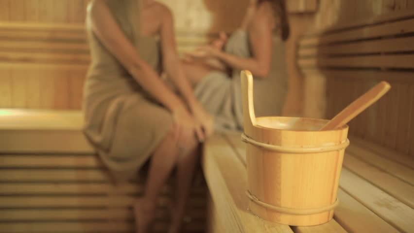A wooden bucket with spoon on blurred background with girls relaxing in sauna