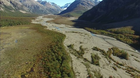 AERIAL shot, drone flies through steep Patagonia landscape in a rocky mountain valley with river navigating through a floodplain of autumn colors.