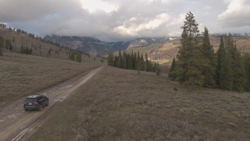 AERIAL: Black SUV car driving on muddy road trough beautiful river valley past pine trees towards majestic Rocky Mountains in Wyoming USA. Off road jeep traveling on gravel road under cloudy mountains
