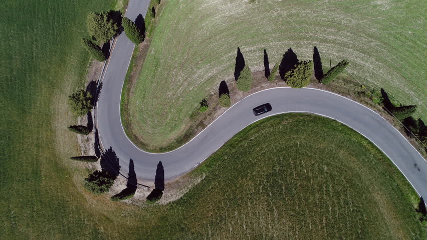 Aerial - Black car driving uphill on winding road with cypress trees | Shutterstock HD Video #28815508