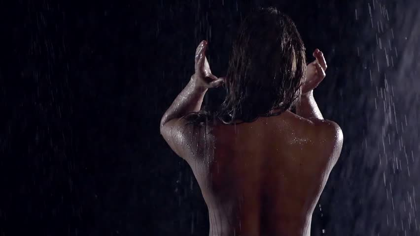 naked woman under a sheet of water collects hair, turns his head, smiling, looking at the camera. water flows down the back. the woman tosses hair, shakes his head. hair fly.