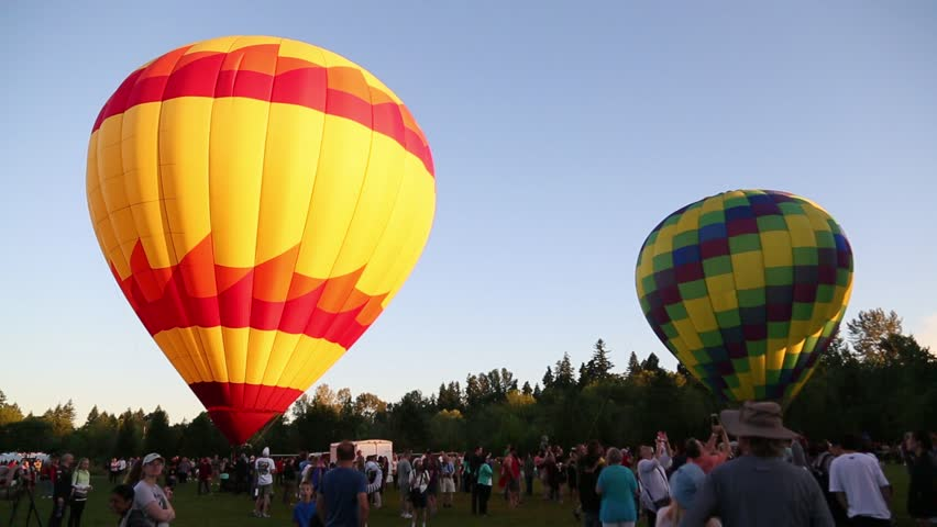 June 25th, 2017, 5:45 am Tigard Festival of Balloons, Cook Park, Tigard Oregon. Hot air balloons stand ready to lift off, in the early morning light, as crowds of the public look on.