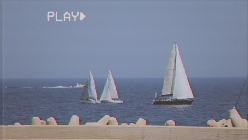 Fake VHS tape: many sailboats at sea, near a pier, in a calm day, getting ready for a regatta.