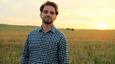 Close up portrait of smiling man standing in green wheat field on sunset and looking at the camera.
