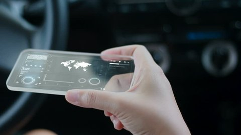 Close up shot hands of woman using clear glass smart phone in the car for futuristic cyber technology concept
