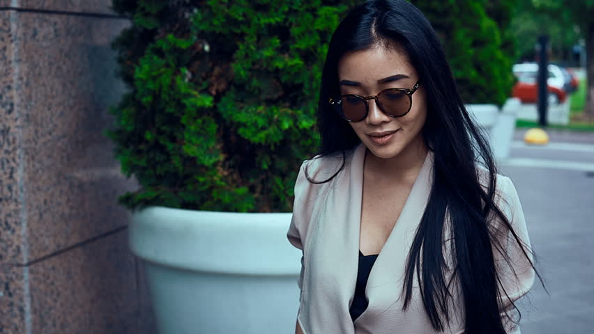 Portrait of a cute and gorgeous asian woman in fashion coat walking along bright european streets