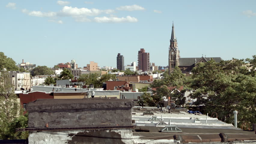 St Stanislaus Kostka Church steeple. Rooftops of Brooklyn, New York. Wide view. View from behind the chimney in Greenpint, polish neighborhood. Trees in the wind. Sunny day. Hand held camera work.