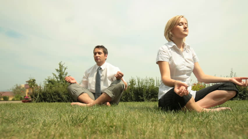 Young business people relaxing outdoors in lotus pose after long working hours